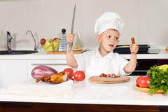 Little boy wielding a large knife in the kitchen Royalty Free Stock Image