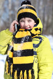 Little boy in a winter park. Little boy calling by phone in a winter park stock images
