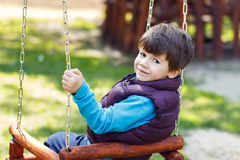 Little boy in winter waistcoat swinging Stock Photo