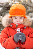 The little boy at the winter walk. Keeps Santa Claus in his hands. New year, holiday, Christmas Stock Photo