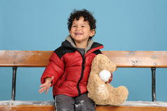 Little boy wit teddy bear seated on a bench Stock Photography