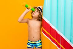 Free Little Boy With Curly Hair In Swimsuit With Rubber Mattress  On Yellow Background Stock Images - 173257314