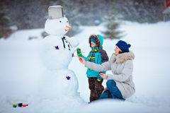 Little Boy With His Mother Painting A Snowman Stock Photo