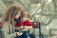 Little boy and woman on the bench. Pretty girl babysits adorable boy. Little boy and pretty girl on the wooden bench Royalty Free Stock Photo
