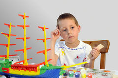 Little boy - woodcraft ship painting, thinking Royalty Free Stock Photos