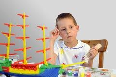 Little boy - woodcraft ship painting, thinking. Cute little boy, woodcraft ship, painting, concentrated, thoughtful; isolated on neutral grayish background Royalty Free Stock Photos