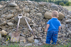 Little Boy at Work. Little boy looking at a pile of rocks and shovel, anticipating all the work ahead of him Royalty Free Stock Photo