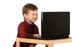 Little boy working on a laptop. Cute smiling little boy working on a laptop computer isolated on white background Royalty Free Stock Image