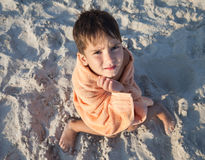 Little boy wrapped in towel sitting on sandy beach Royalty Free Stock Images