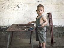 Little boy with a wrench standing at the wall Royalty Free Stock Image