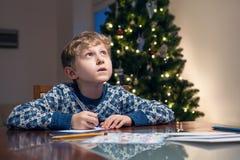Little boy write Christmas wishes to Santa Stock Image