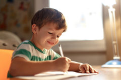 Little boy write into exercise book Stock Photo