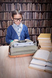 Little boy writer on desk with typewriter in library Stock Photography