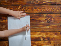 Little boy writes in notebook sitting at desk Royalty Free Stock Photography