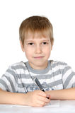 The little boy writes to writing-books a ball pen Stock Photos