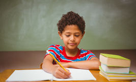 Little boy writing book in classroom Royalty Free Stock Image