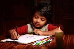 Little boy writing with a burning candle Royalty Free Stock Photo