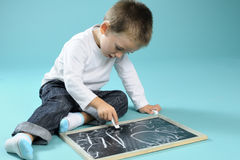 Little boy writing with chalk on black board Royalty Free Stock Photos
