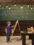 Little boy writing on chalkboard. Side view kid in front of green board with math equation. Smart little fellow studying. Math royalty free stock photo