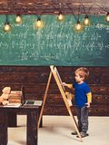Little boy writing on chalkboard. Side view kid in front of green board with math equation. Smart little fellow studying. Math royalty free stock photos