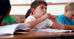 Little boy writing during class. In elementary school stock video
