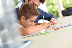 Little boy writing homewrok with help of his father. Man helping son with homework stock images