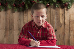 Little boy writing a letter for Santa Stock Images