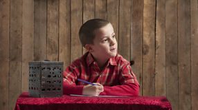 Little boy writing a letter for Santa Stock Image