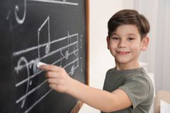 Little boy writing music notes on blackboard stock images