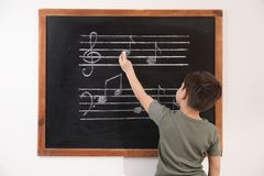 Little boy writing music notes on blackboard royalty free stock images