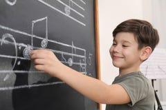 Little boy writing music notes on blackboard royalty free stock photo