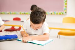 Little boy writing on a notebook in school stock images