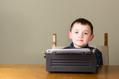 Little boy writing on an old typewriter smiling Royalty Free Stock Images