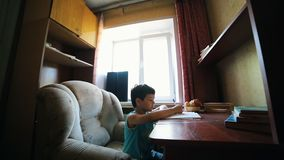 A little boy writing something in the notebook - doing homework stock video footage
