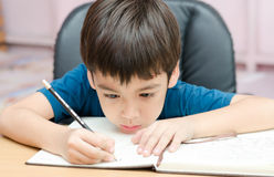 Little boy writing and thinking homework Royalty Free Stock Image
