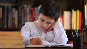 Little boy writing and thinking stock video footage
