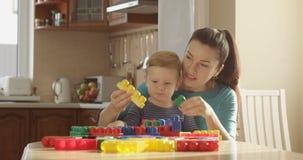 Little Boy y la mamá están jugando a los juegos que desarrollan habilidades de motor y creatividad finas almacen de metraje de vídeo