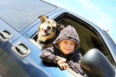 Little Boy y su perro que cuelgan hacia fuera la ventana del minivan Foto de archivo