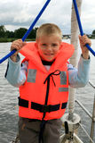 Little boy on yacht. Boy in the life jacket on the yacht. He is pulling sheets (ropes). Sailing Stock Photography