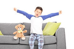 Little boy yawning seated on couch Stock Image