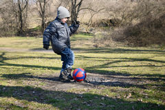 Little boy 6-7 years hits the ball to score a goal Royalty Free Stock Photography