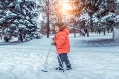 Little boy 3-5 years old, in the park in the winter walks on children`s skis. Happy smiling plays, first steps in sport. Little boy 4-6 years old, in the park in royalty free stock image