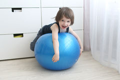 Little boy (3 years) playing with a big blue ball at home Royalty Free Stock Photos