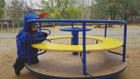 The little boy of 4 years shakes himself on a roundabout in playground. Child smiling and laughing. Spring cloudy weather. Blue and yellow carousel. Slow stock video
