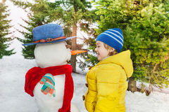 Little boy in yellow with beautiful snowman Royalty Free Stock Image