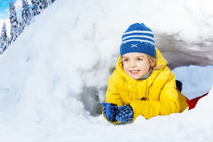 Little boy in yellow crawl through snow tunnel Royalty Free Stock Photos