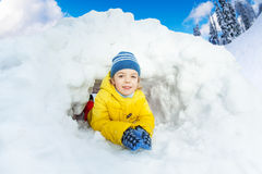 Little boy in yellow inside snow cave Stock Photo