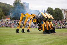 Three JCB loaders suspended on buckets with wheels in the air stock images