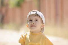 Little boy in yellow looking up Stock Photography
