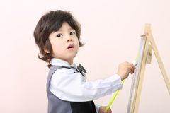 Little boy with yellow pointer draws with chalk on chalkboard Royalty Free Stock Images